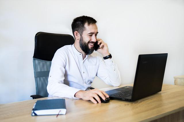 muž sedí za stolem v bílé košili, sedí u černého notebooku, telefonuje a usmívá se, vedle má notes